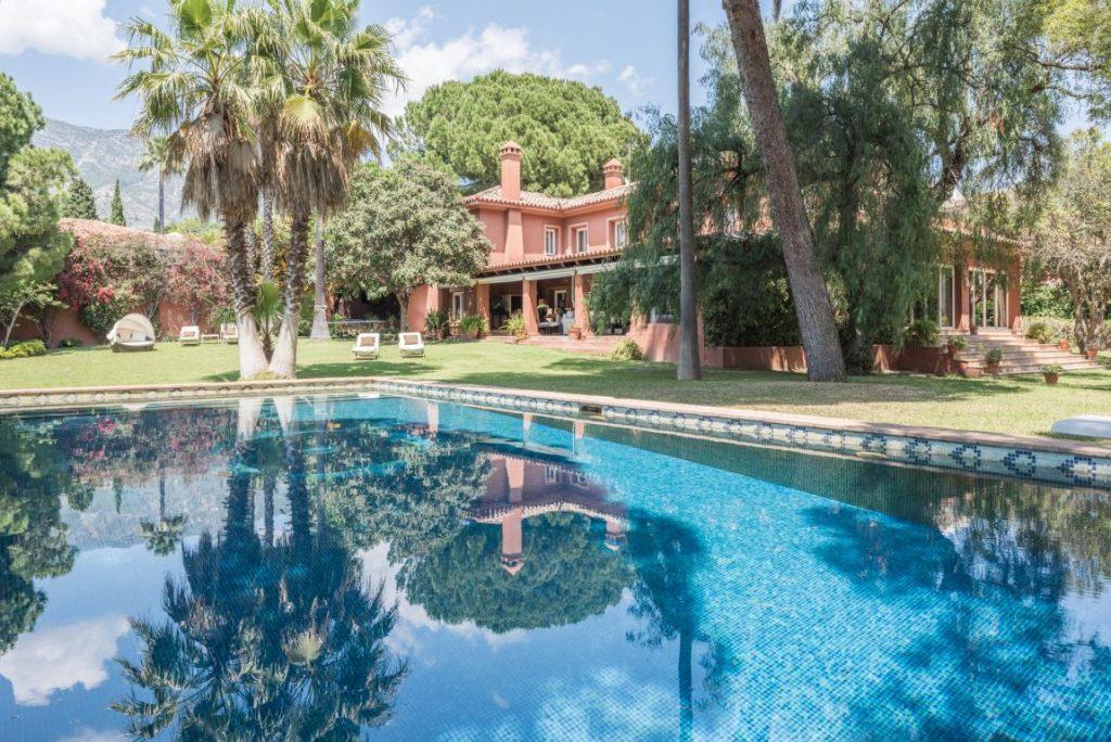 Casa en estilo tradicional  español sureño, entre vegetacion y con una piscina enorme
